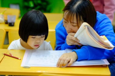 teacher guides student with reading